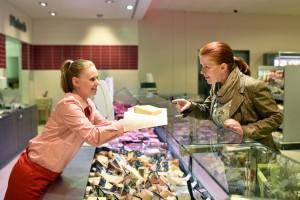 junge Verkäuferin  bedient Kundin an Käsetheke im Supermarkt